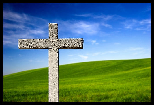 Religious stone cross on a beautiful green hill